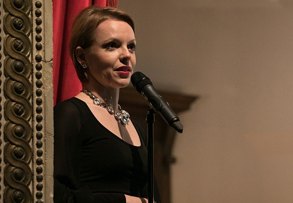 Magdalena Baczewska: woman with short blond hair, dressed in black and wearing a silver-colored necklace singing into a mic.