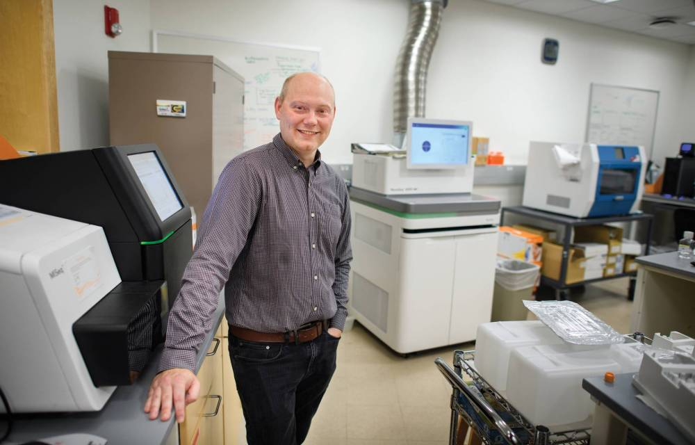 Joshua Akey surrounded by machines that help analyze DNA samples