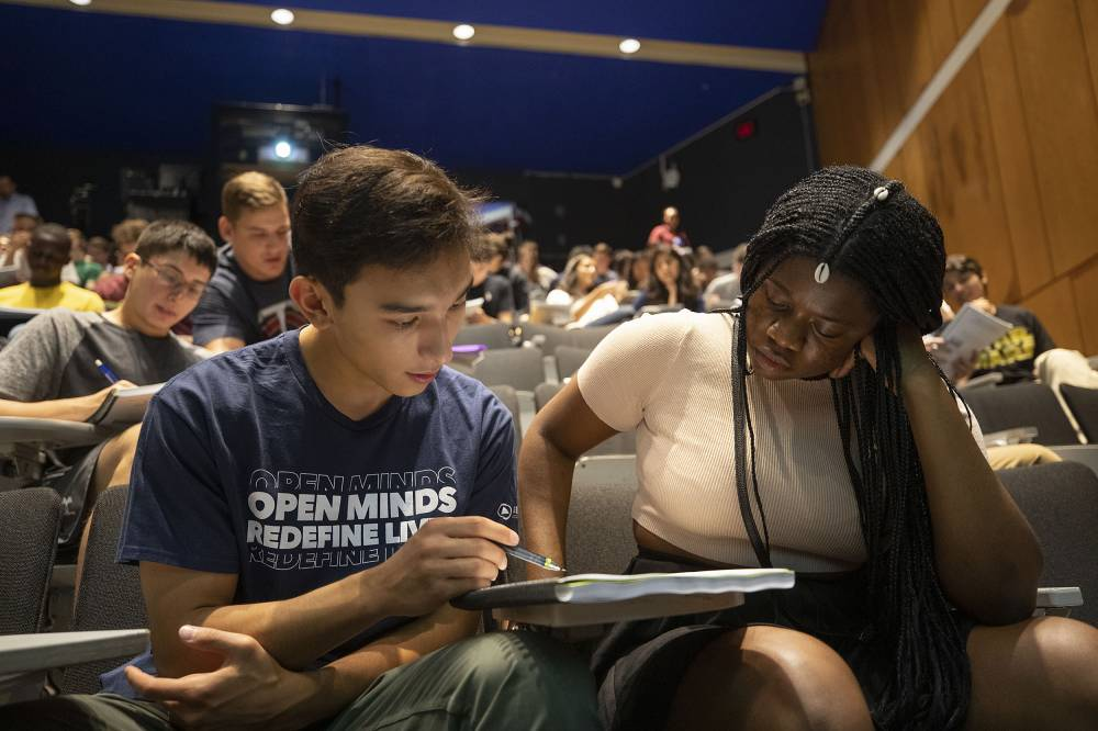 Two students studying together in a lecture hall.