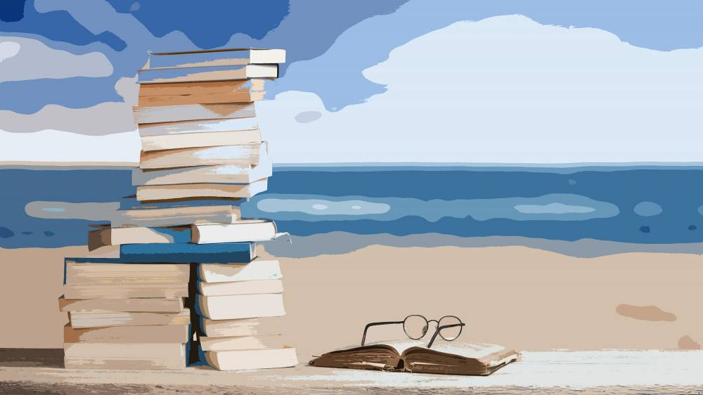 Stack of books on a beach.