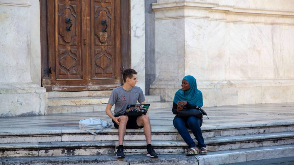 Student interviewing young immigrant sitting on steps