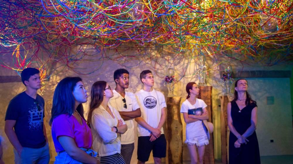 Students standing underneath art installation