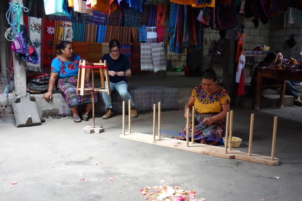 A student sits with 2 weavers
