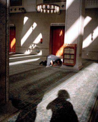 A person kneeling in a shadowy room