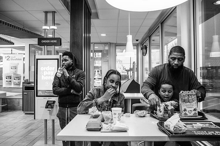 Roland Whitley sits with his son and two people at McDonalds.