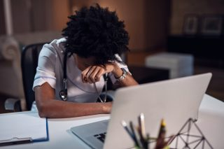 Tired doctor rests her head on her hand in front of a computer. ©Getty Images