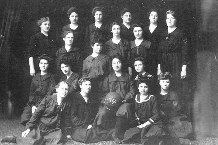Women wearing black uniforms pose with a basketball.