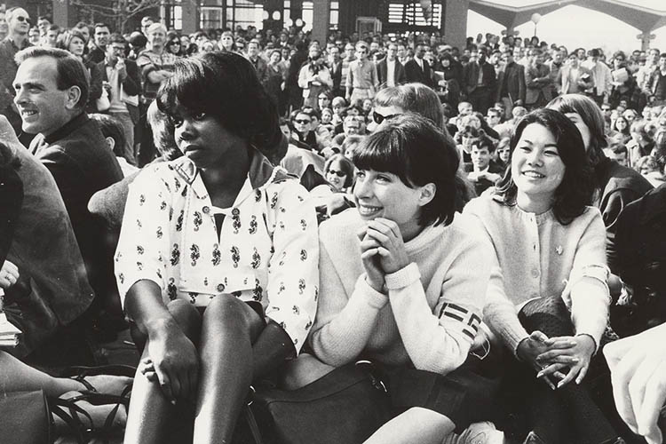 Three women sit on the ground listening to a speaker amidst a crowd of people.