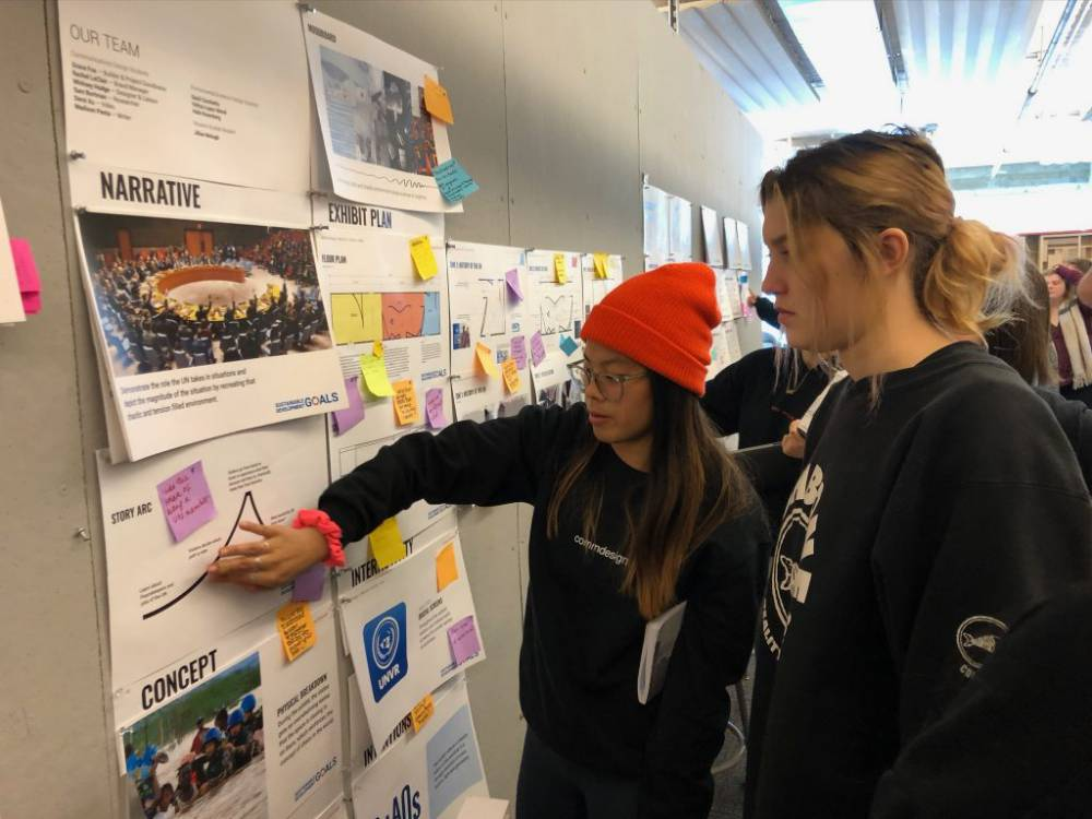 students looking at papers on a display board
