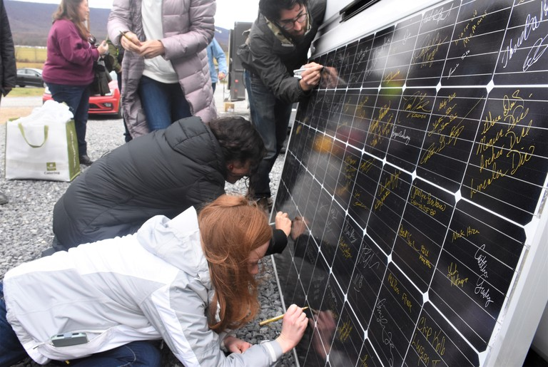 Penn State graduate students sign a solar panel.