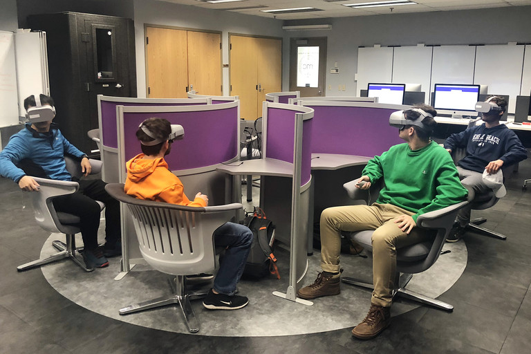 Four students travel on a virtual field trip using Oculus Go headsets at one of several virtual reality labs on campus.