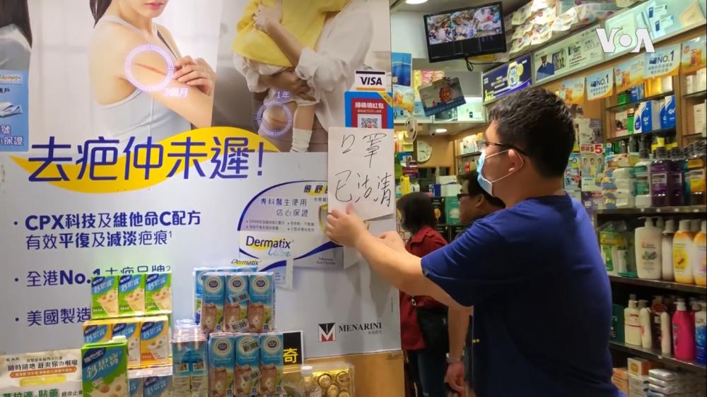 A pharmacy employee hangs a sign written in Chinese