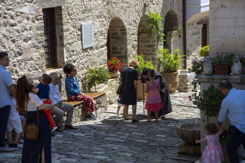 A nun bows her head in conversation with a family