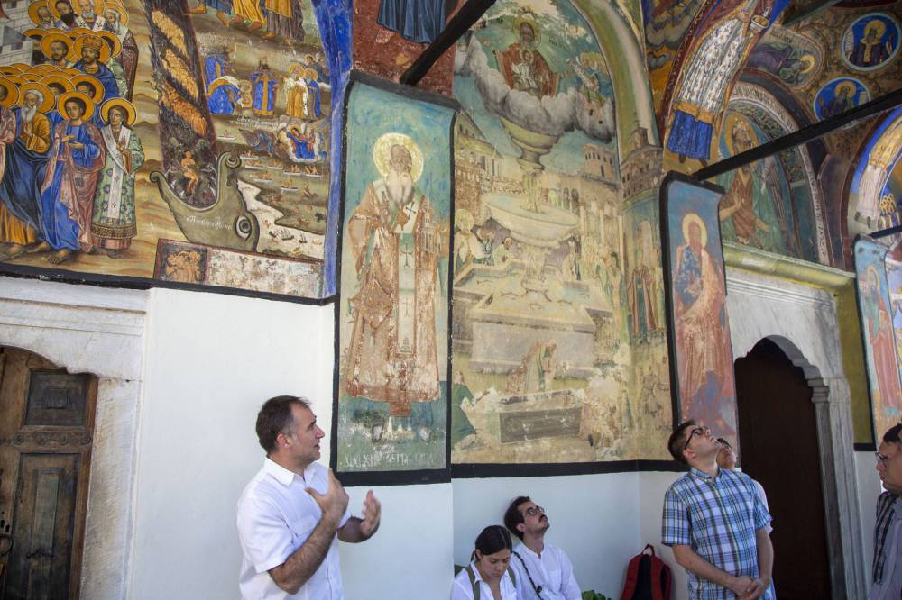 A lecturer talks about the Byzantine paintings on the walls of the monastery