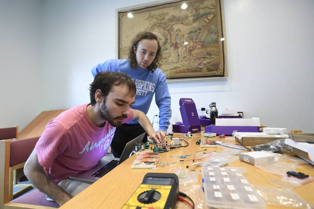 Jacob Young (front) and Collin Champagne troubleshoot their device
