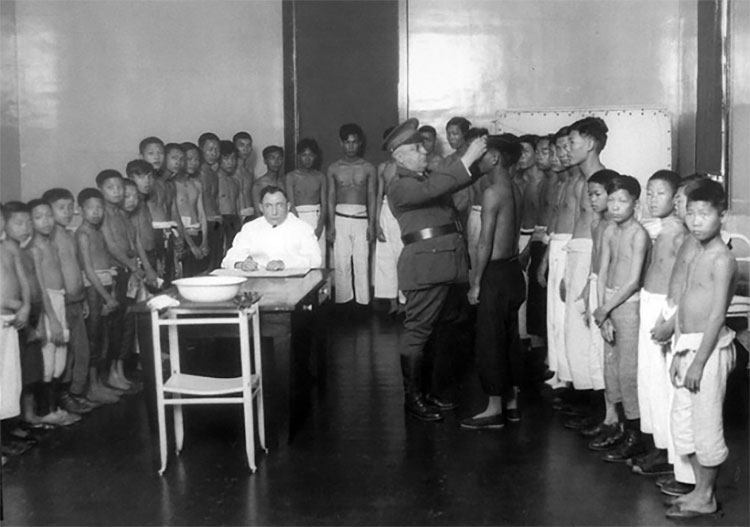 A group of men and boys without shirts on in a line as a man with a military uniform inspects them.
