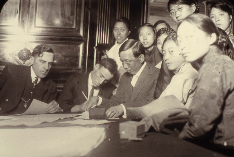 An old photo of a group of people at a table signing documents.