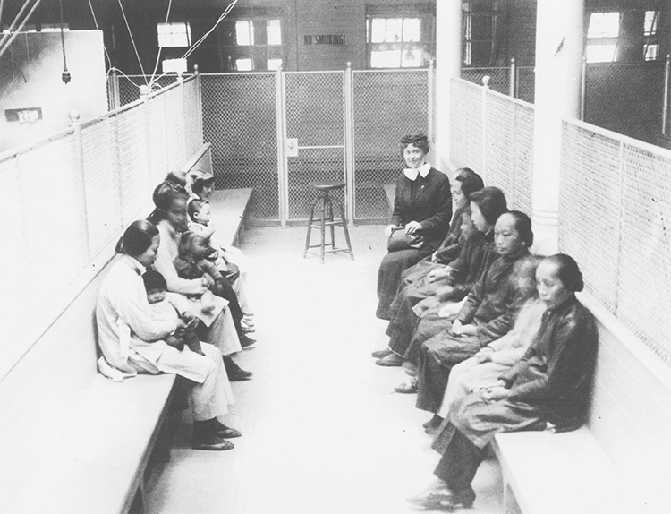 A group of women sitting on benches in a caged area.
