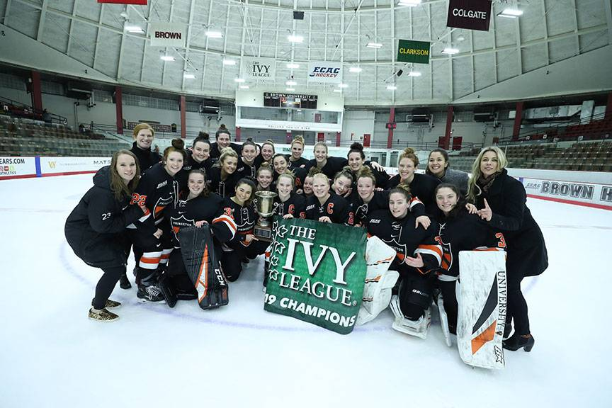 Princeton women's ice hockey team poses with their Ivy League Championship banner