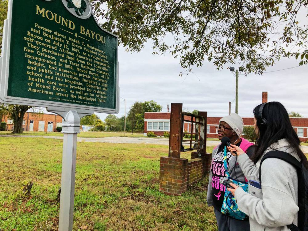 A student interviews the mayor of Mound Bayou next to a historical plaque