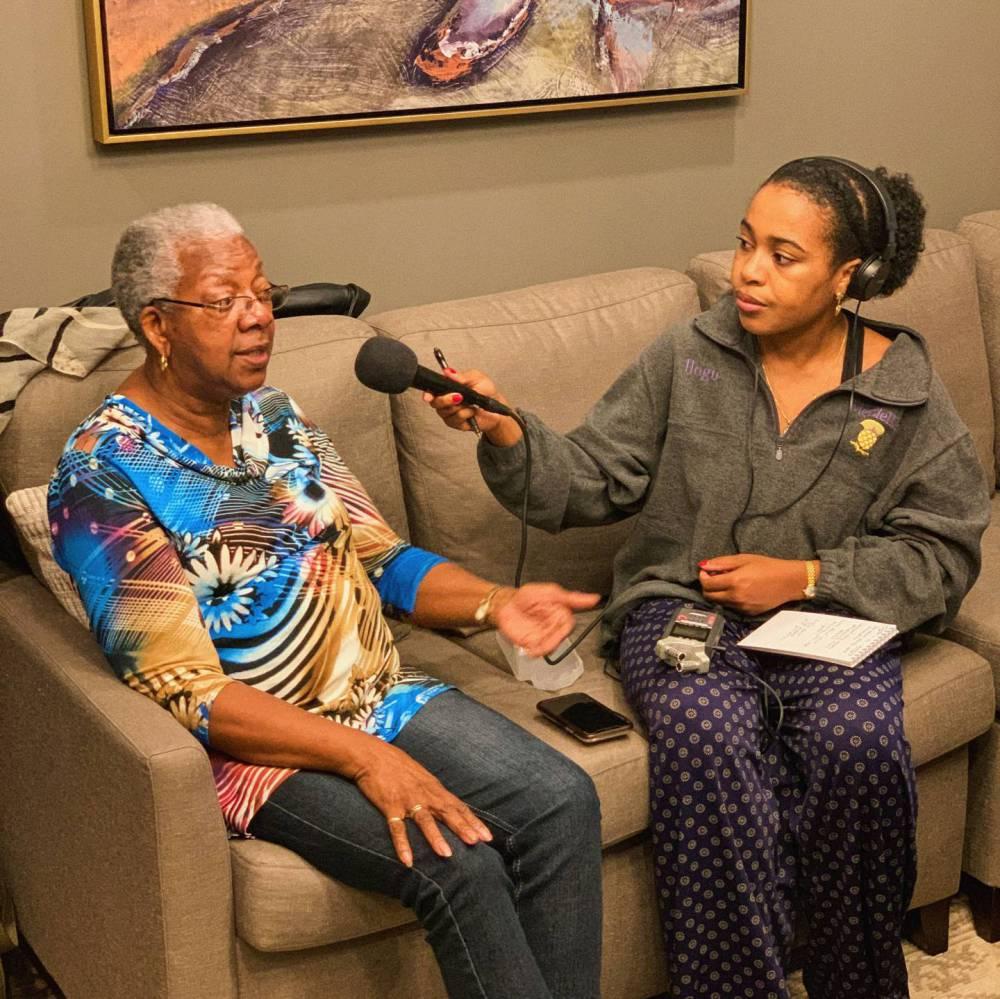 A student interviews a woman on a tan sofa