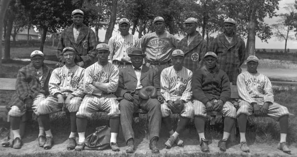 Members of the Chicago American Giants pose for a team portrait in 1914. Rube Foster is seated in the center of the first row wearing a suit.
