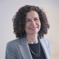 Jessica Justman with short curly hair, wearing a gray blazer and black blouse.