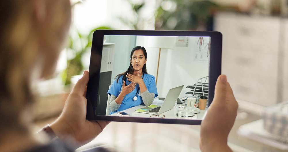A physician administers a telehealth checkup with a patient virtually