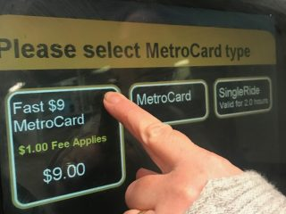 Finger touching screen to purchase Metrocard