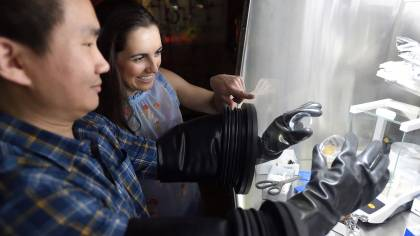 A man uses gloves in a protective box while a woman looks on