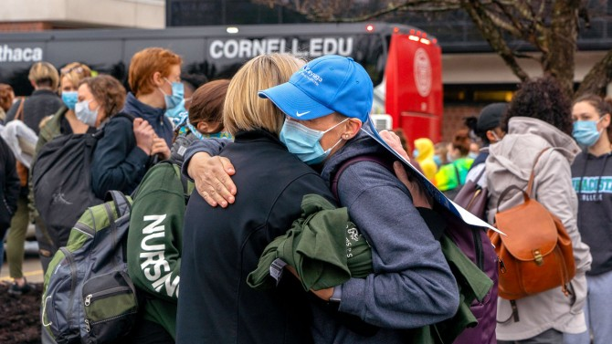 Health care giver gives hug before boarding bus
