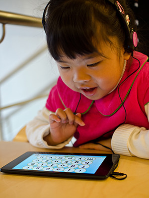 Young girl playing on a tablet