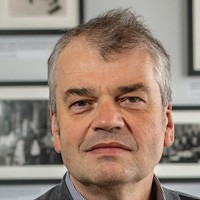 Dmitri Basov: A man with closely cropped grey hair staring into the camera with framed black and white photos behind him.