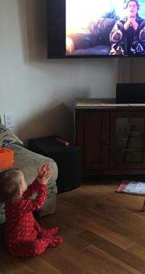 child watches video of teacher singing