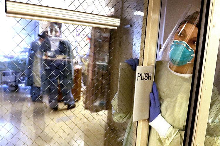 A nurse waits in an open doorway in a hospital ICU