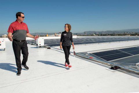 Mike Bohn and Carol L. Folt check out Galen Center solar panels