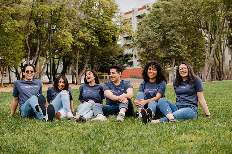 The staff of Central Valley Scholars in matching grey t-shirts sit on the grass.