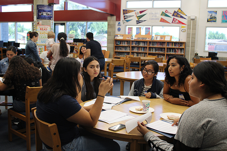 Students discuss a topic in a high school library