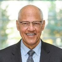 Wilmot James: A bald, bespectacled man, wearing a suit and tie, smiling into the camera.