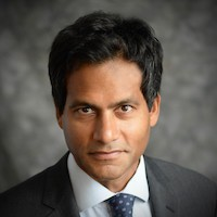 Jameel Jaffer from the Knight Institute: Dark haired man wearing gray suit, white shirt and blue tie with gray dots.