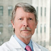 A grey-haired man with mustache and beard, wearing blue button-down shirt, pink tie and white lab coat.