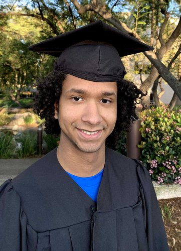 A portrait of Kenny Duran wearing a graduation robe and mortarboard.