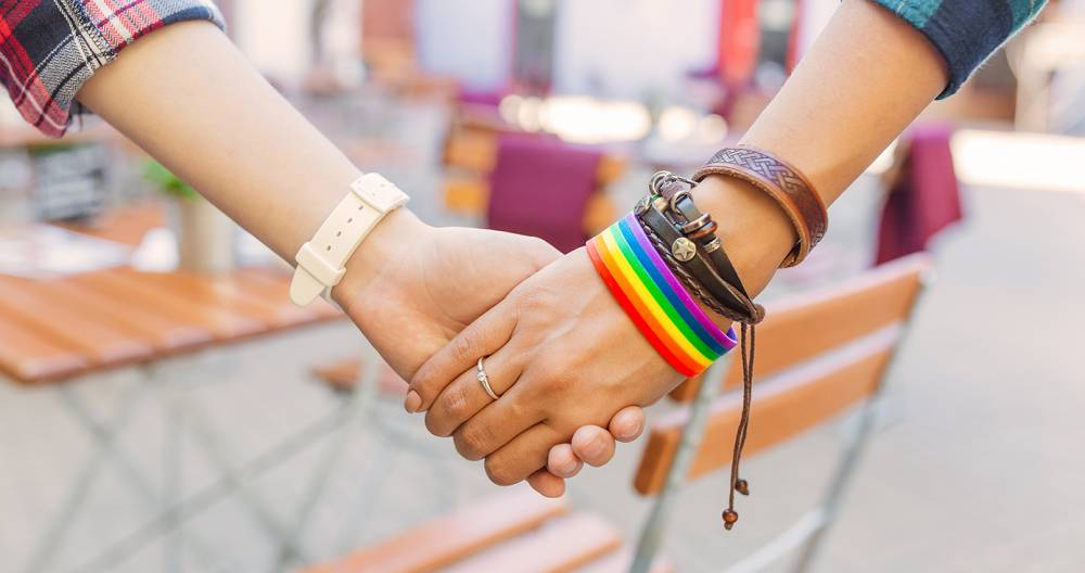 a close-up of two people holding hands, one wearing a watch and the other wearing a rainbow bracelet