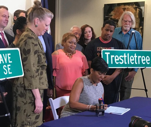 An African American woman is seated signing at the desk surrounded by people with street signs next to her.