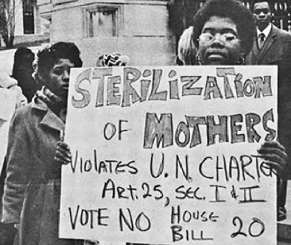 A black and white photo showing women protesting holding up signs.