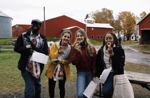 Four students stand together outside holding donuts