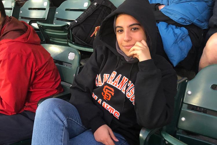 Maryam Al Hosani at a baseball game in an SF Giants sweatshirt