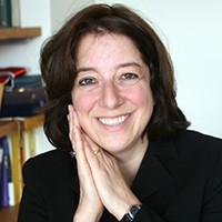 Anya Schiffrin in a black blazer with her hands clasped by her face