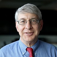 Thomas Kent: A man with gray hair, eyeglasses, wearing a blue shirt and red tie.