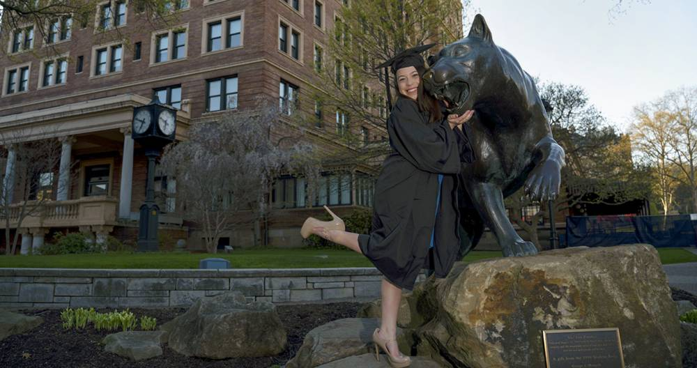 A woman in a black graduation cap and gown posing with a statue of a panther